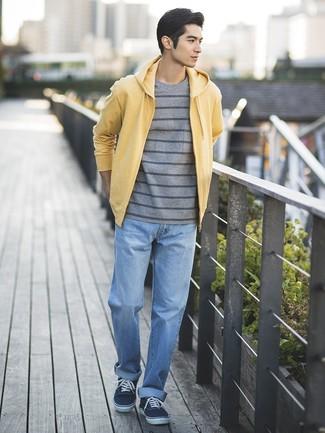 Cómo combinar: tenis de lona azul marino, vaqueros celestes, camiseta con cuello circular de rayas horizontales gris, sudadera con capucha amarilla