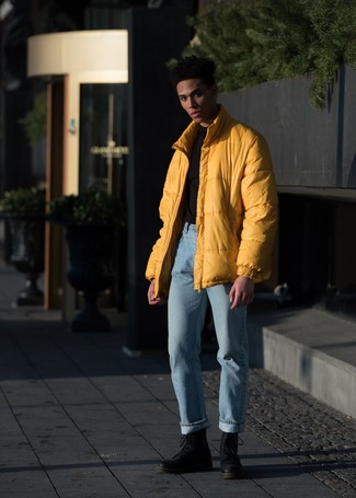 Outfits hombres: Emparejar un plumífero amarillo con unos vaqueros celestes es una opción práctica para un día en la oficina. Botas casual de cuero negras son una sencilla forma de complementar tu atuendo.