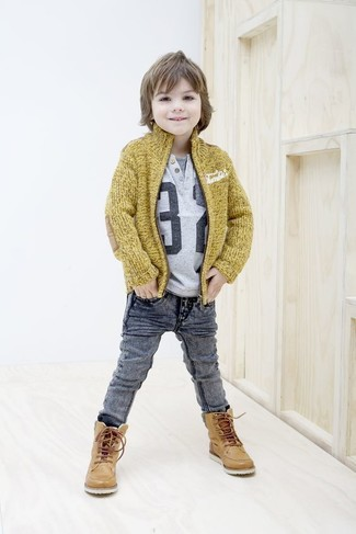 Cómo combinar: botas de cuero marrón claro, vaqueros grises, camiseta estampada gris, cárdigan mostaza