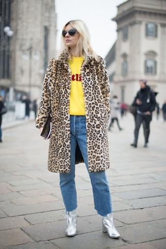 Cómo combinar: botines de cuero plateados, vaqueros azules, jersey con cuello circular estampado amarillo, abrigo de piel de leopardo marrón claro