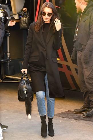 Cómo combinar: botines de elástico negros, vaqueros con adornos azules, jersey con cuello circular negro, abrigo negro