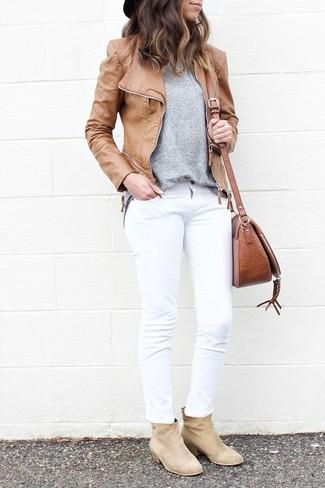 Cómo combinar: botines de ante en beige, vaqueros blancos, jersey con cuello circular gris, chaqueta motera de cuero marrón claro