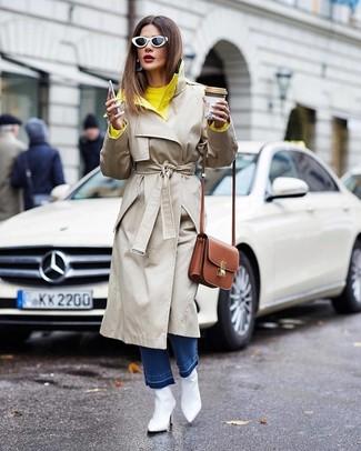 Cómo combinar: botines de cuero blancos, vaqueros azules, jersey con cuello circular amarillo, gabardina en beige