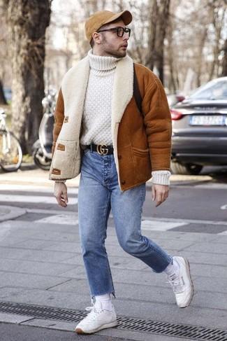 Cómo combinar: tenis de cuero blancos, vaqueros azules, jersey de cuello alto de lana de punto blanco, chaqueta de piel de oveja en tabaco