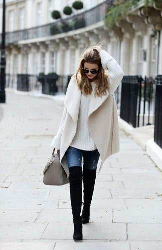 Cómo combinar: botas sobre la rodilla de ante negras, vaqueros azules, jersey oversized de punto blanco, chaleco de piel de oveja en beige