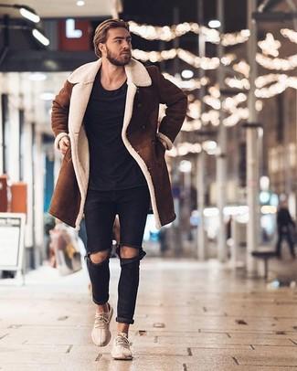 Cómo combinar: deportivas en beige, vaqueros desgastados negros, camiseta con cuello circular negra, abrigo de piel de oveja marrón