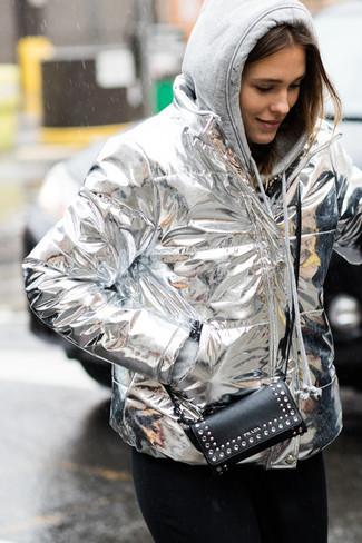 Cómo combinar: cartera sobre de cuero con tachuelas negra, vaqueros negros, sudadera con capucha gris, plumífero plateado