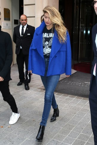 Cómo combinar: botines de cuero negros, vaqueros pitillo azul marino, camiseta con cuello circular estampada en negro y blanco, chaquetón azul