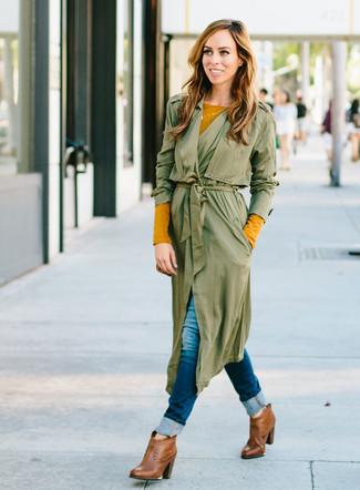 Cómo combinar: botines de cuero marrónes, vaqueros pitillo azul marino, camiseta de manga larga mostaza, abrigo duster verde oliva