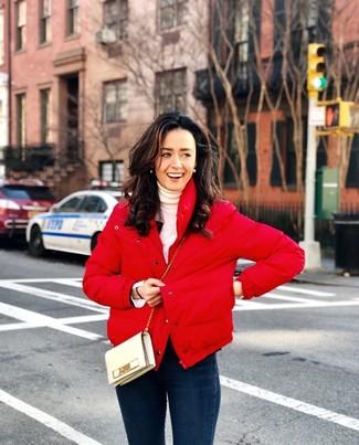 Cómo combinar: bolso bandolera de cuero en beige, vaqueros pitillo azul marino, jersey de cuello alto blanco, plumífero rojo