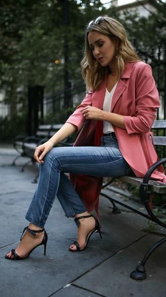 Cómo combinar: sandalias de tacón de cuero negras, vaqueros pitillo azules, camiseta sin manga de seda blanca, abrigo duster rosado