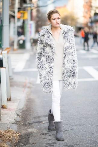 Cómo combinar: botas ugg grises, vaqueros pitillo blancos, sudadera con capucha de punto en beige, abrigo de piel gris