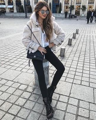 Cómo combinar: botas planas con cordones de ante negras, vaqueros pitillo negros, blusa de botones de gasa blanca, chaqueta de piel en beige