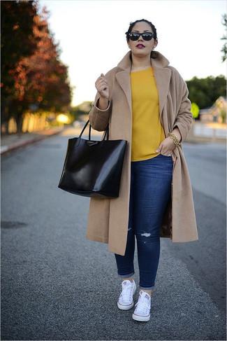 Cómo combinar: tenis de lona blancos, vaqueros pitillo desgastados azul marino, blusa de manga corta amarilla, abrigo marrón claro
