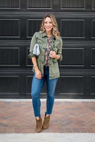 Cómo combinar: botines de ante marrónes, vaqueros pitillo desgastados azules, blusa de manga corta con print de flores azul marino, chaqueta militar verde oliva
