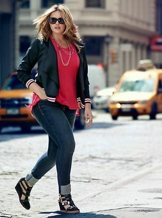 Cómo combinar: sandalias con cuña de ante negras, vaqueros pitillo azul marino, blusa de manga corta roja, chaqueta motera de cuero negra