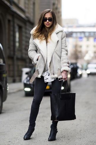 Cómo combinar: botines de cuero negros, vaqueros pitillo negros, blusa de manga larga estampada en blanco y negro, chaqueta de piel de oveja gris