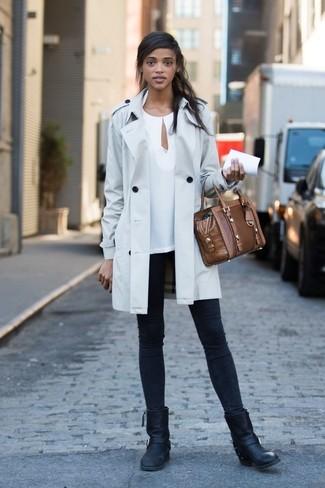 Cómo combinar: botas a media pierna de cuero negras, vaqueros pitillo negros, blusa de manga larga blanca, gabardina gris