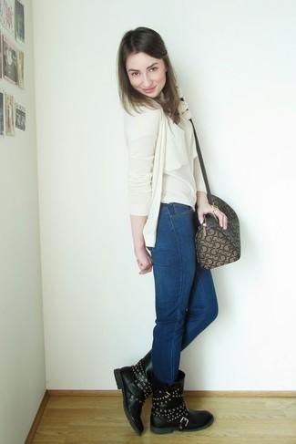 Cómo combinar: botas a media pierna de cuero con tachuelas negras, vaqueros pitillo azul marino, blusa sin mangas en beige, cárdigan en beige