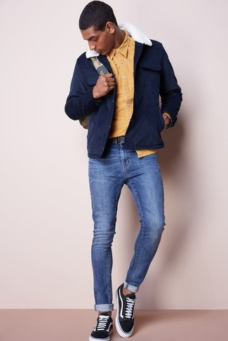 Cómo combinar: tenis de lona negros, vaqueros pitillo azules, camisa de manga larga amarilla, chaqueta campo de ante azul marino