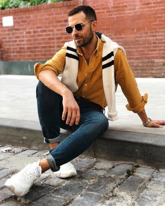 Cómo combinar: deportivas blancas, vaqueros pitillo azul marino, camisa de manga larga mostaza, jersey con cuello circular de rayas horizontales en beige