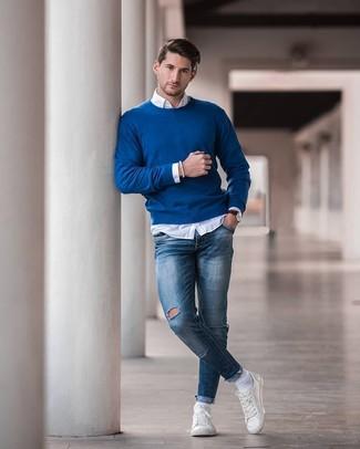 Cómo combinar: tenis de cuero blancos, vaqueros pitillo desgastados azules, camisa de manga larga blanca, jersey con cuello circular azul