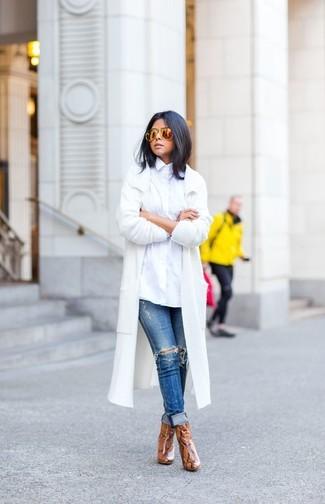 Cómo combinar: botines de cuero con print de serpiente marrónes, vaqueros pitillo desgastados azules, camisa de vestir blanca, abrigo blanco