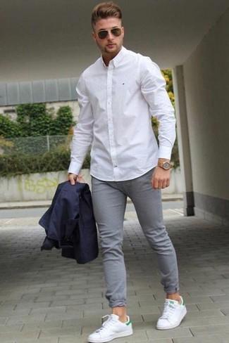 Cómo combinar: tenis de cuero blancos, vaqueros pitillo grises, camisa de vestir blanca, blazer azul marino