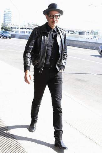 Cómo combinar: botines chelsea de cuero negros, vaqueros pitillo negros, camisa de vestir negra, cazadora de aviador de cuero negra