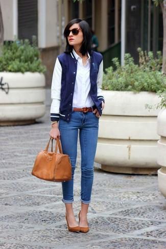 Cómo combinar: zapatos de tacón de ante marrónes, vaqueros pitillo azules, camisa de vestir blanca, chaqueta varsity en azul marino y blanco