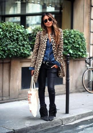 Cómo combinar: botines de ante сon flecos negros, vaqueros pitillo de cuero negros, camisa vaquera azul, abrigo de piel de leopardo marrón claro
