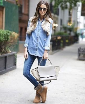 Cómo combinar: botas ugg marrón claro, vaqueros pitillo azules, camisa vaquera celeste, bolero de pelo en beige
