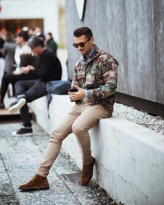 Cómo combinar: botas formales de ante marrónes, vaqueros pitillo en beige, camisa vaquera azul, chaqueta militar de camuflaje verde oliva