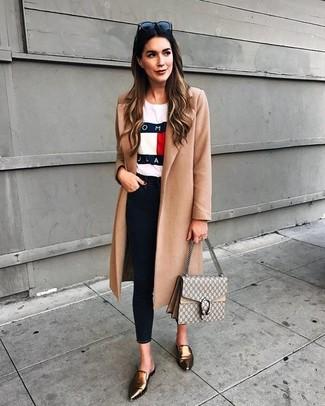Cómo combinar: mocasín de cuero dorados, vaqueros pitillo negros, camiseta con cuello circular estampada blanca, abrigo marrón claro