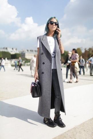 Cómo combinar: botas planas con cordones de cuero negras, vaqueros pitillo en gris oscuro, camiseta con cuello circular estampada en blanco y negro, abrigo sin mangas gris