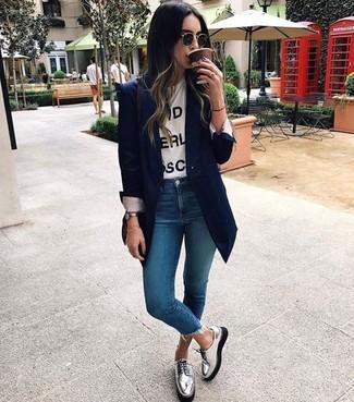 Cómo combinar: zapatos derby de cuero plateados, vaqueros pitillo azules, camiseta con cuello circular estampada en blanco y negro, blazer azul marino