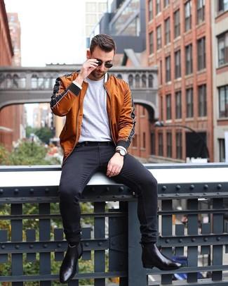 Cómo combinar: botines chelsea de cuero negros, vaqueros pitillo negros, camiseta con cuello circular gris, cazadora de aviador en tabaco