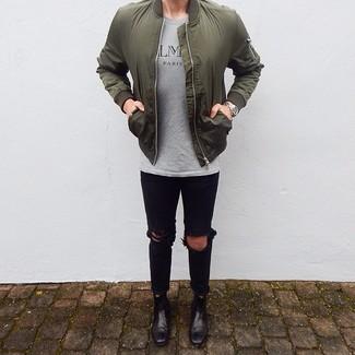 Cómo combinar: botines chelsea de cuero negros, vaqueros pitillo desgastados negros, camiseta con cuello circular estampada gris, cazadora de aviador verde oliva