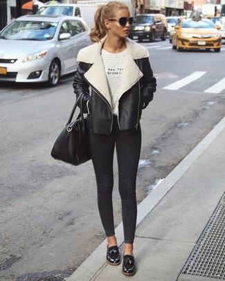 Cómo combinar: mocasín de cuero negros, vaqueros pitillo negros, camiseta con cuello circular estampada gris, chaqueta de piel de oveja en negro y blanco