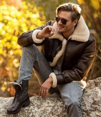 Cómo combinar: botas casual de cuero en marrón oscuro, vaqueros pitillo grises, camiseta con cuello circular gris, chaqueta de piel de oveja en marrón oscuro