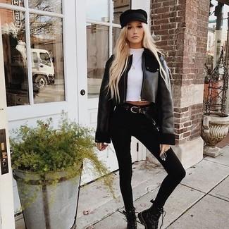Cómo combinar: botas planas con cordones de cuero negras, vaqueros pitillo negros, camiseta con cuello circular blanca, chaqueta de piel de oveja negra