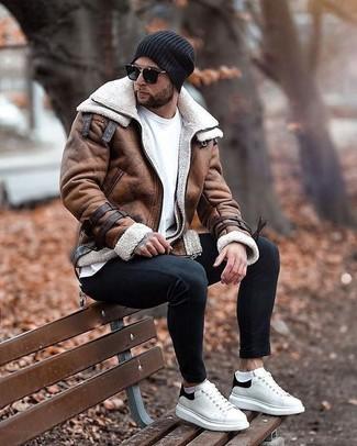Outfits hombres en invierno 2020: Para crear una apariencia para un almuerzo con amigos en el fin de semana intenta combinar una chaqueta de piel de oveja marrón junto a unos vaqueros pitillo negros. Tenis de cuero en blanco y negro son una opción perfecta para completar este atuendo. ¡Nos gusta el look! Es una opción buena para tus días de invierno.
