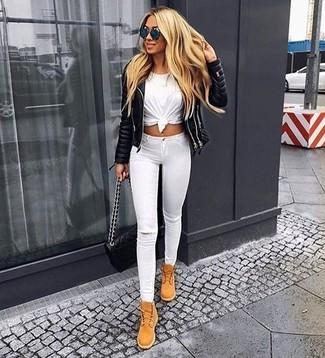 Cómo combinar: botas planas con cordones de ante marrón claro, vaqueros pitillo desgastados blancos, camiseta con cuello circular blanca, chaqueta motera de cuero acolchada negra