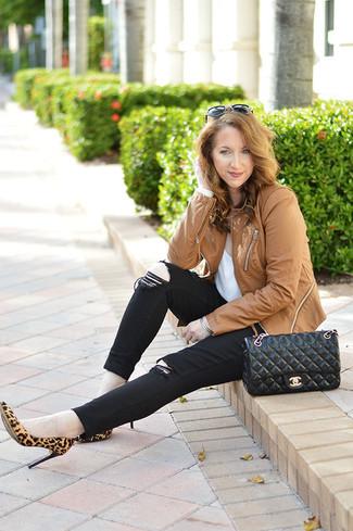 Cómo combinar: zapatos de tacón de ante de leopardo marrón claro, vaqueros pitillo negros, camiseta con cuello circular blanca, chaqueta motera de cuero marrón claro