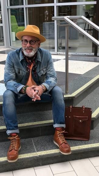 Cómo combinar: botas de trabajo de cuero marrónes, vaqueros pitillo azules, camiseta con cuello circular naranja, chaqueta vaquera azul