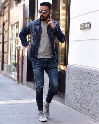 Look de moda: Tenis de lona grises, Vaqueros pitillo desgastados azul marino, Camiseta con cuello circular estampada gris, Chaqueta vaquera azul marino