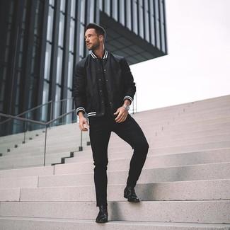 Cómo combinar: botines chelsea de cuero negros, vaqueros pitillo negros, camiseta con cuello circular negra, chaqueta varsity en negro y blanco