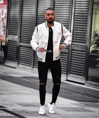 Cómo combinar: tenis de cuero blancos, vaqueros pitillo desgastados negros, camiseta con cuello circular negra, chaqueta varsity en blanco y negro