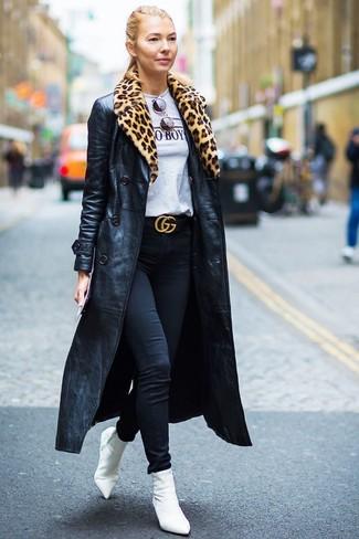 Cómo combinar: botines de elástico blancos, vaqueros pitillo negros, camiseta con cuello circular estampada gris, gabardina de cuero negra