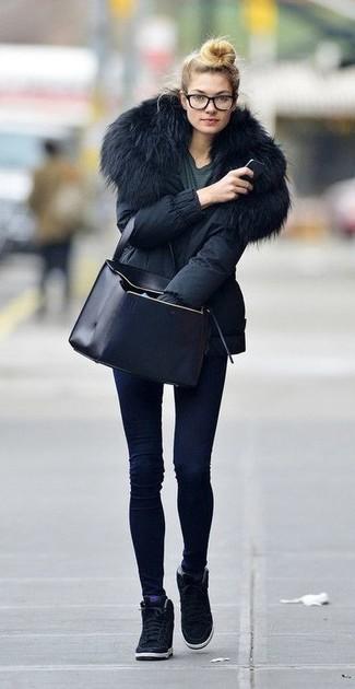Cómo combinar: zapatillas con cuña de ante negras, vaqueros pitillo azul marino, camiseta con cuello circular en gris oscuro, parka negra